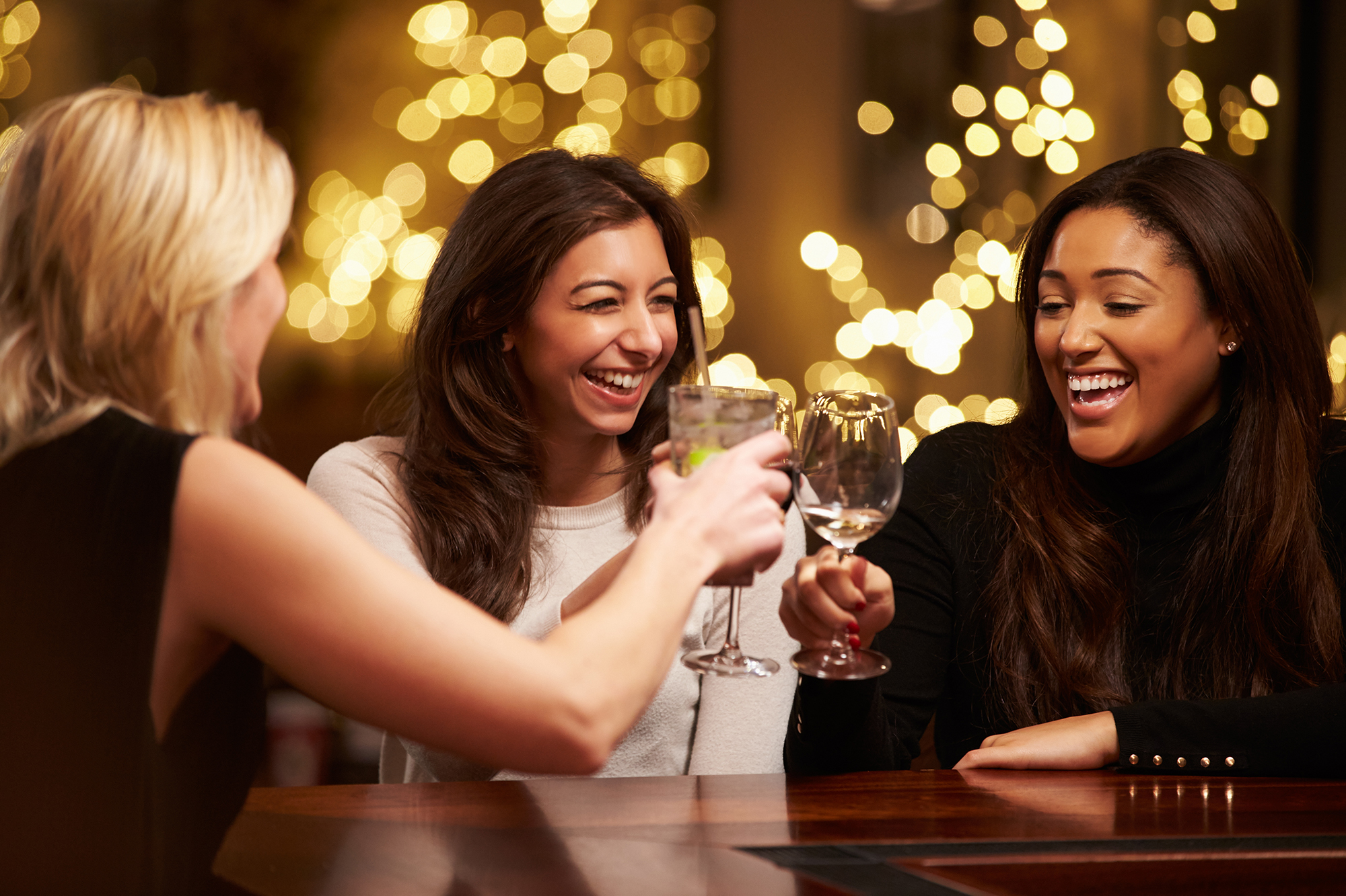 Group Of Female Friends Enjoying Evening Drinks In Bar